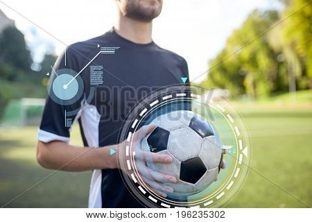 sport, football training and technology - close up of soccer player with ball on field