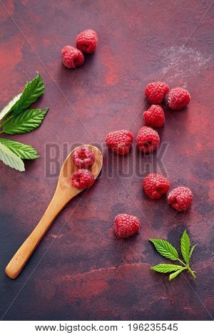A fresh raspberry on a wooden spoon. Ripe fresh raspberries with leaves on rustic background.