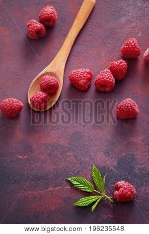 Raspberries with spoon. A fresh raspberry on a wooden spoon. Ripe fresh raspberries with leaves on rustic background.