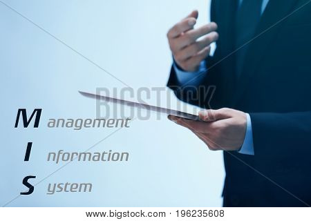 Concept of management information system. Businessman using tablet on color background, closeup