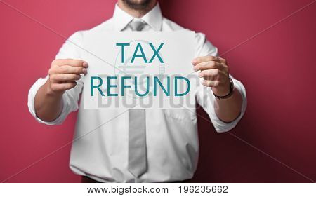 Businessman holding paper with text TAX REFUND on color background