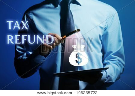 Man holding magnifier and tablet on dark background. Tax refund concept