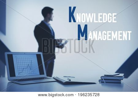 Concept of knowledge management. Workplace with laptop and man on background