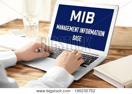 Concept of management information base. Man using laptop at wooden table