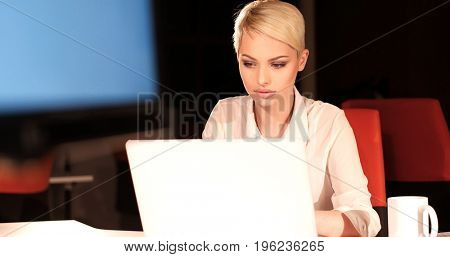 young female entrepreneur working on laptop computer in night office
