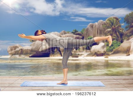 fitness, people and healthy lifestyle concept - woman doing yoga warrior pose on half-bent right leg on mat over exotic tropical beach background