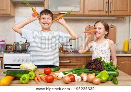 Child girl and boy having fun with tomatoes and carrot. Home kitchen interior with fruits and vegetables. Healthy food concept