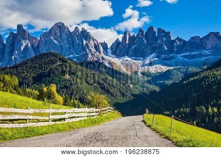 The road descends into the Val de Funes. Warm autumn in the Dolomites. The concept of ecological tourism. Rocky peaks and forested mountains surrounded by green Alpine meadows