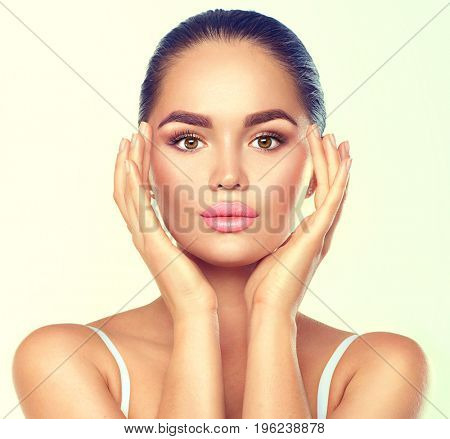 Beauty Portrait. Beautiful Spa Brunette Woman Touching her Face. Perfect Fresh Skin. Pure Beauty Model Girl. Youth and Skin Care Concept.