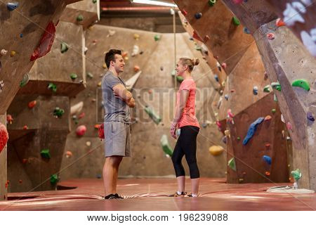 fitness, extreme sport, bouldering, people and healthy lifestyle concept - man and woman talking at indoor climbing gym