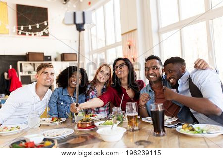 leisure, technology and people concept - group of happy international friends eating and taking picture by smartphone selfie stick at restaurant