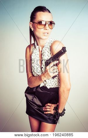 Beautiful female spy holding hand gun