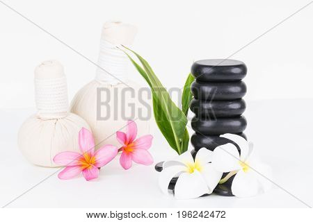 Spa with herbal compress balls, hot stones and flowers on white background