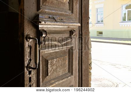 Half-open old wooden brown door on the background of old city.