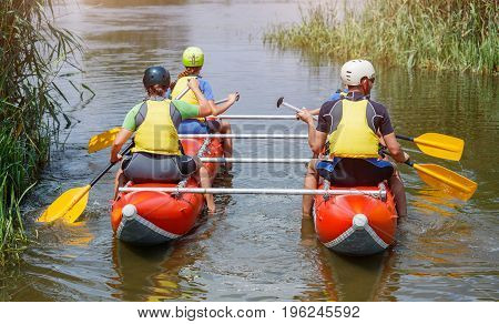 Happy family of four wearing life vests and helmets on the catamaran. Rafting family on holidays