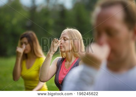 A yoga girl in nature performs breathing exercises with a group, summer
