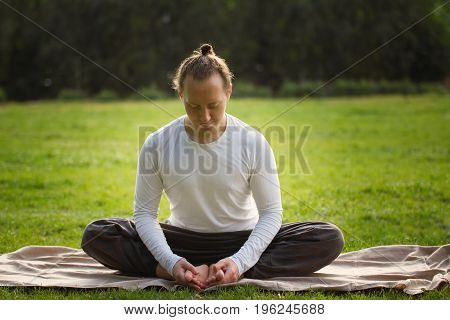 The yoga instructor in the lotus posture relaxes after exercising, outdoor
