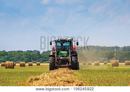 Tractor in a farmer field with balls of straw.