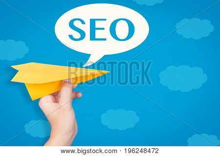 hand holding paper plane with seo in speech bubble on blue background illustration
