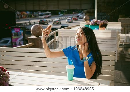 Cute Asian Young Woman In Summer Cafe Outdoors. Girl In A Blue Dress, With Long Hair In Simple Light