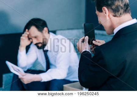 smirking businessman holding smartphone holding smartphone and photographing upset fired colleague sitting on stairs