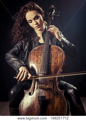 Photo of a beautiful female musician playing a cello.