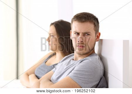 Angry couple after argument looking at another side sitting on the bed at home