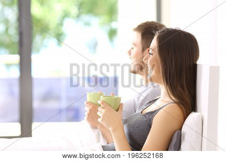 Side view of a couple looking outside in the bedroom sitting on a bed of an apartment with a green background outdoors