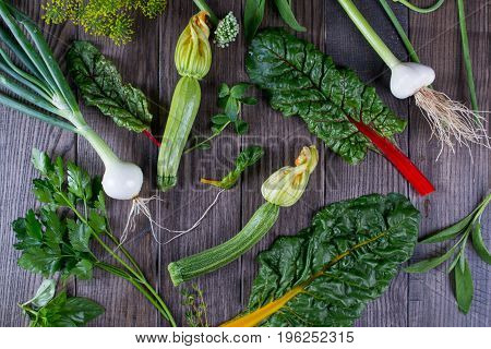 Assortment of fresh  vegetables and herbs on dark rustic background. Cooking background