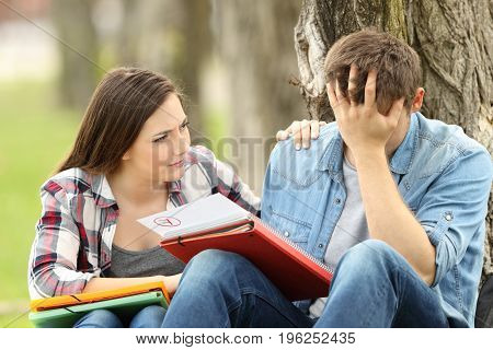 Friend comforting to a sad student with failed exam sitting on the grass in a park