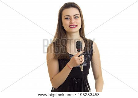 cheerful young woman in black dress smiles with microphone in hands isolated on white background