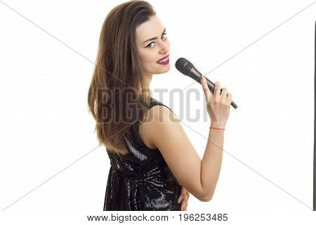 cutie young woman in black dress with microphone in hands isolated on white background