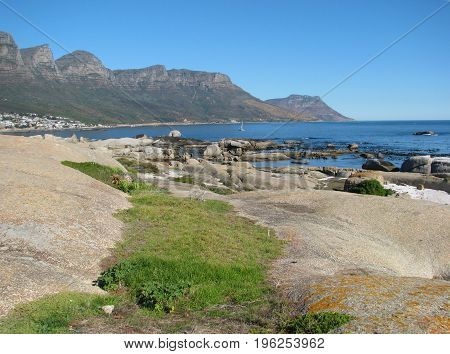 VIEW OF CAMPS BAY, CAPE TOWN, SOUTH AFRICA, WITH HUGE BOULDERS AND LAWN IN THE FORE GROUND AND MOUNTAINS IN THE BACK GROUND
