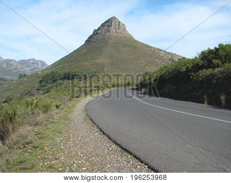 FROM CAPE TOWN, SOUTH AFRICA,  A ROAD IN THE FORE GROUND LEADING TO LIONS HEAD IN THE BACK GROUND ON A SLIGHTLY CLOUDY DAY