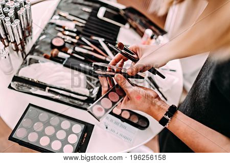 Hands of a makeup artist. Cosmetics on a wooden workplace. Eyeshadow, blushes, powder, professional cosmetics and makeup brushes. Workplace makeup artist.