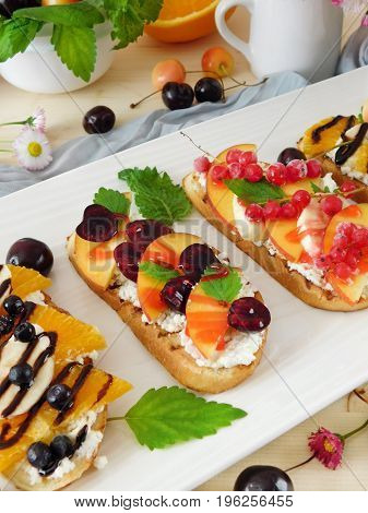 Bruschetta with berries, fruits and cream cheese on a white plate. Italian restaurant dish
