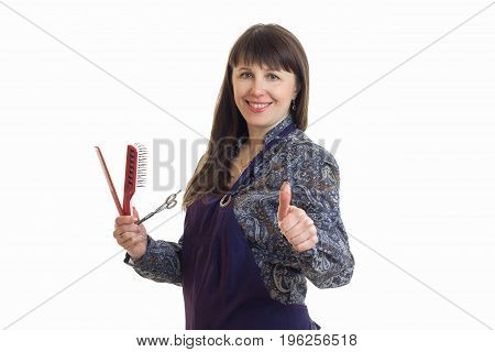 cheerful stylist woman in upron with tools in hands shows thumbs up isolated on white background