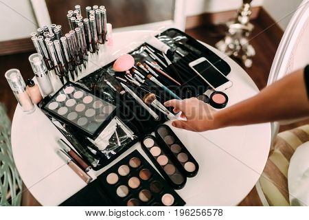 Hands of a makeup artist. Many cosmetics and brushes on a table in the salon. Workplace makeup artist. Set of brushes for makeup.