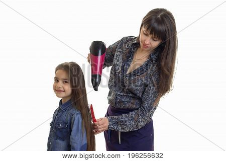 mother makes a hairstyle to her little daughter isolated on white background