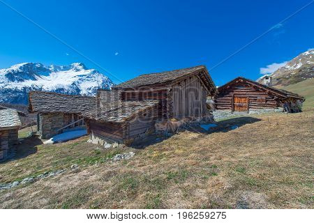 Typical Swiss wooden cabins in high mountain pastures.