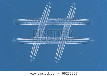 Four airplanes leave contrails in the form of the special sign # Hashtag against a dark blue sky.