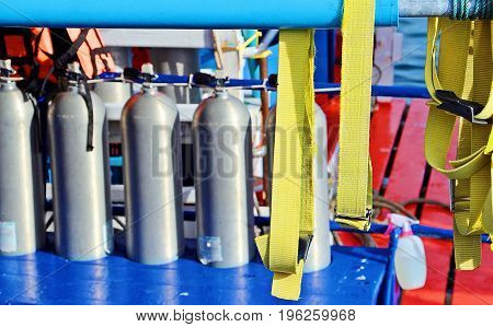 Safety belt with row of scuba diving air tanks as background on boat