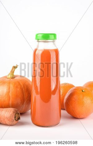 Pumpkin, carrot and orange juice. Vegetable soft drink in a glass bottle isolated on white background