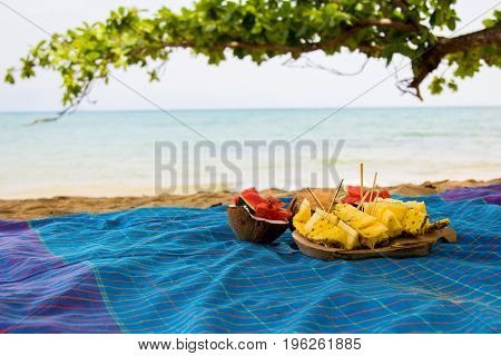 Beautiful set of prepared fruits on vivid blue cloth at the beach side with tree branch in the background