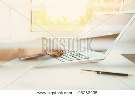 Woman using laptop for browsing internet store at table, closeup. View through window blinds. Online shopping concept