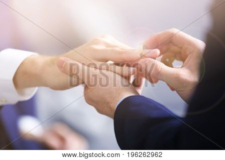 Man putting wedding ring on groom's finger, closeup. Gay rights concept
