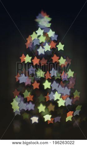 glowing christmas tree with star bokeh on dark backround