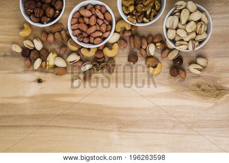 Four Bowls With Nuts On A  Wooden Table.