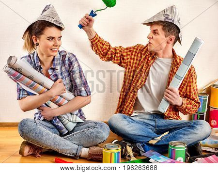 Repair family by happy couple building home . Newlyweds are fooled and quarrel because of renovation in new apartment. Mad woman and man in newspaper cap renovation apartment .
