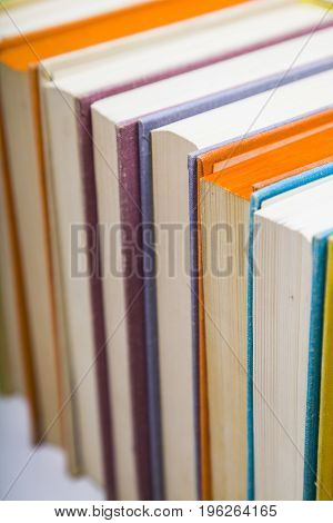 Stack of books on a white background. A lot of books are close-up.